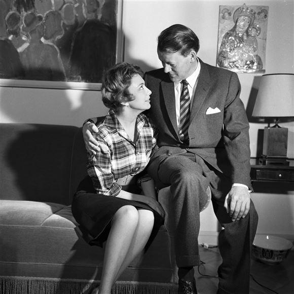 Gammelt ikonisk billede af Helle Virkner og Jens Otto Kragh, Hun sidder på en sofa og smiler kærligt til ham. Han sidder ved siden af hende men på armlænet så han er hævet over hende.