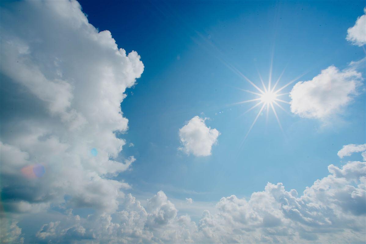 Billed af sol, skyer og blå himmel
