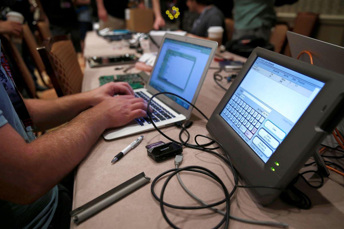 Hacker sidder foran to computere