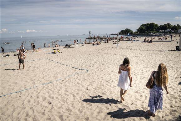 Solbeskinnet strand med sommeklædte mennesker på