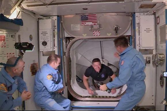 En astronaut kravler igennem slusen på Rumstationen ISS og bliver modtaget af tre andre astronauter