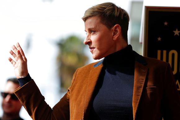 Ellen de Generes i rullekravebluse og brun jakke.