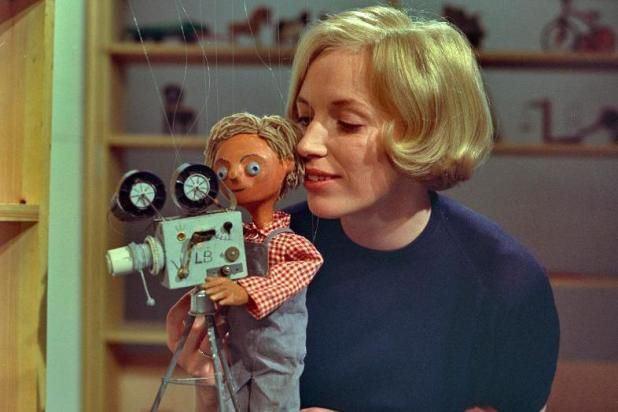 Lillebror-dukken bagved et filmkamera og Ingrid bag ham.
