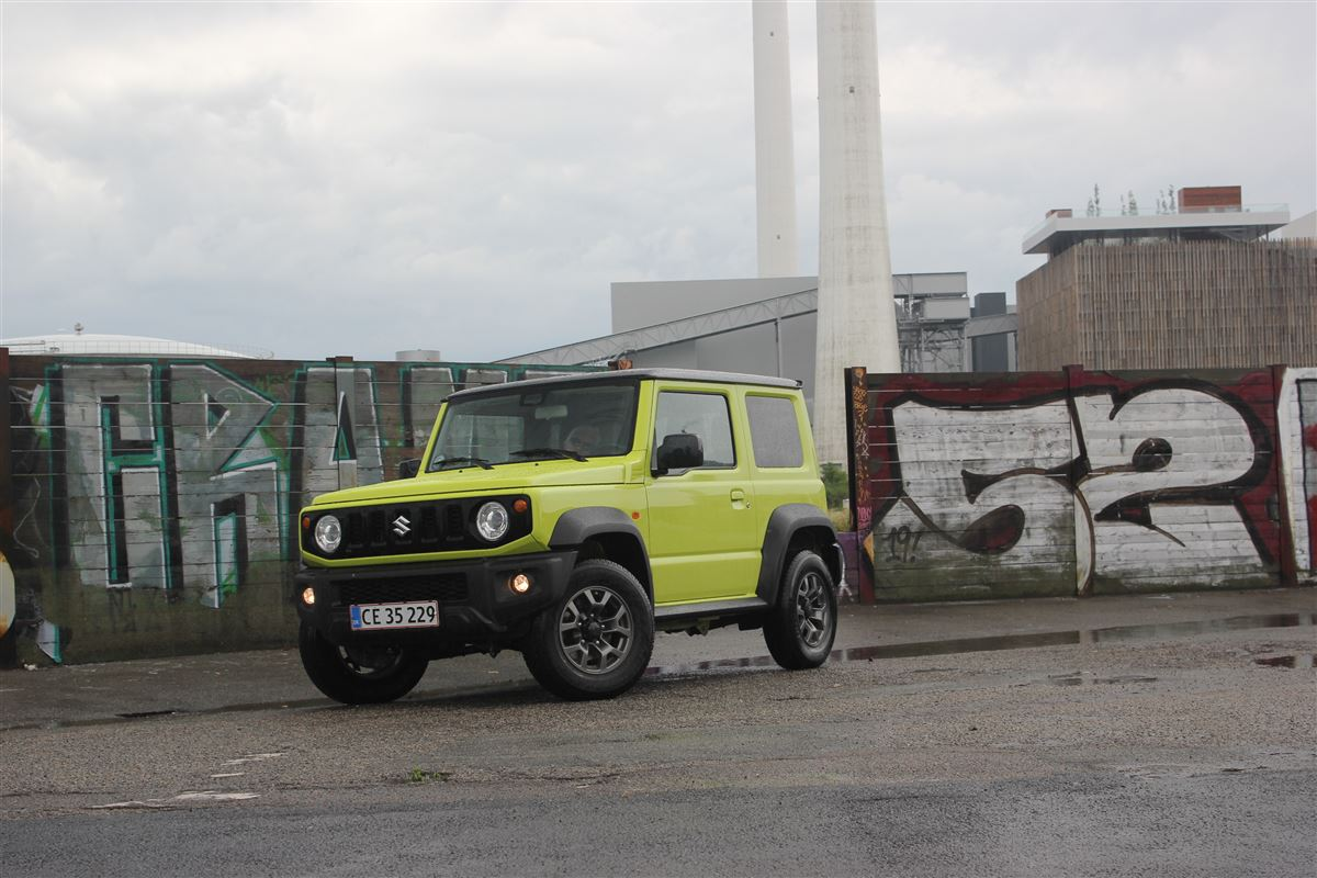 En grøn Suzuki foran grafittimur