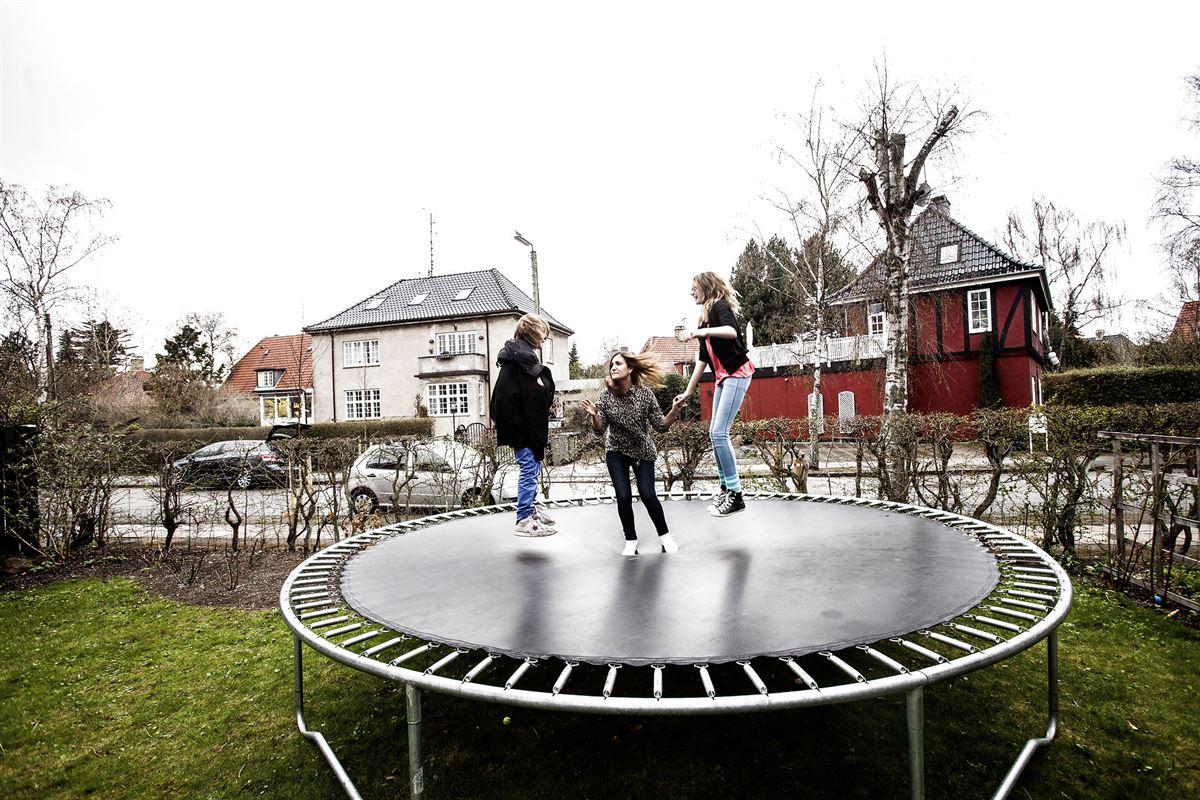 tre børn hopper på en trampolin i haven