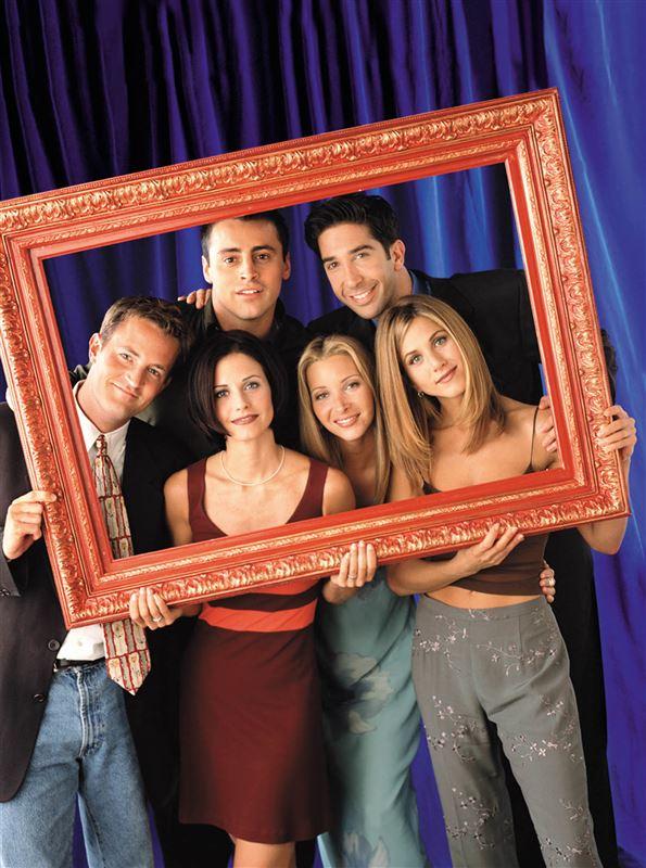 """De seks skuespillere, som udgør """"Friends"""" står bag en tom ramme og smiler."""