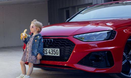 En lille pige med solbriller, som spiser en banan, mens hun læner sig op ad køleren på en bil.