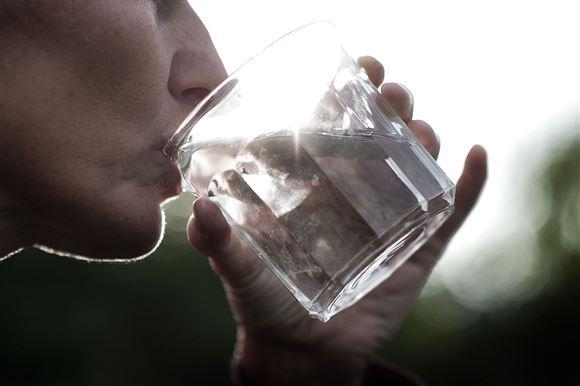 person drikker vand af et glas