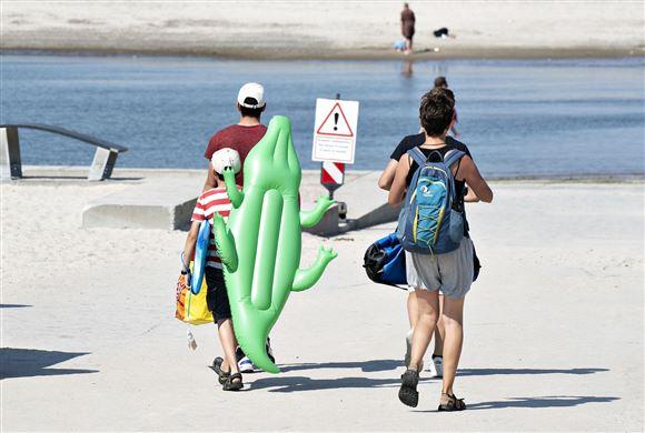 Badegæster går på stranden med et badedyr formet som en krokodille