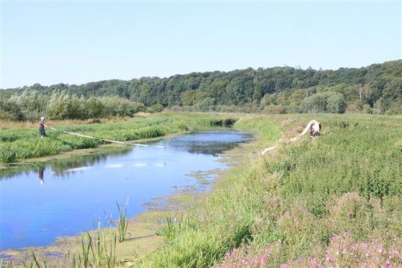 Redningsmandskab i færd med at lægge flydespærringer ud i kanal på Djursland.
