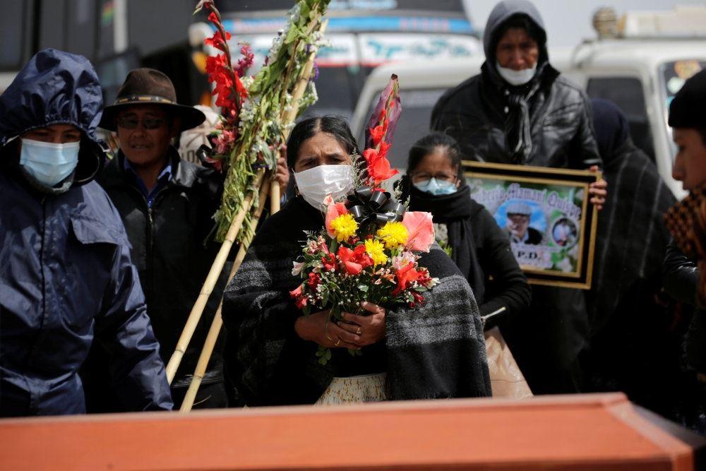 Dame med maske og favnen fuld af blomster til en begravelse
