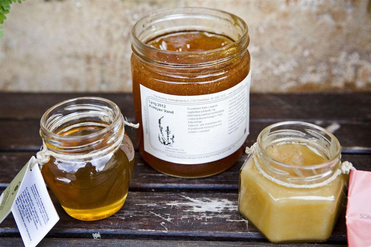 Tre glas honning på et bord