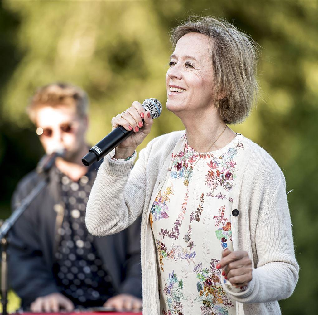 Anne Dorte Michelsen med gråt hår synger i det fri