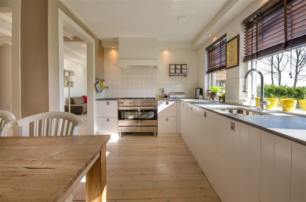 Et smukt køøken med store træpersienner foran vinduerne.