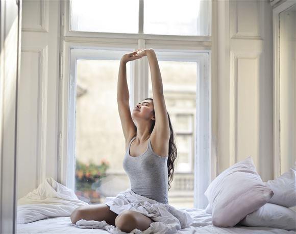 Ung kvinde strækker sig i seng