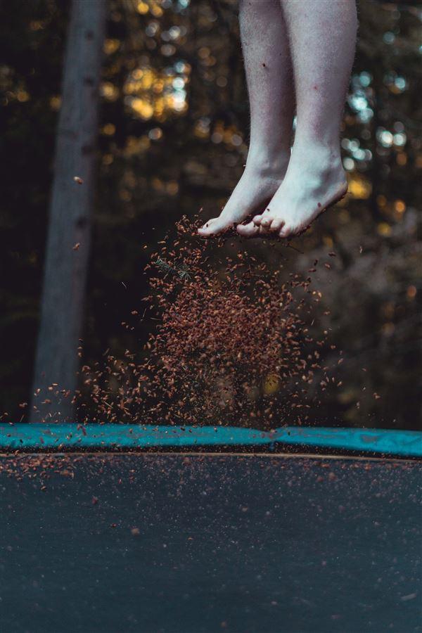 Et par fødder der er på vej ned på en trampolin
