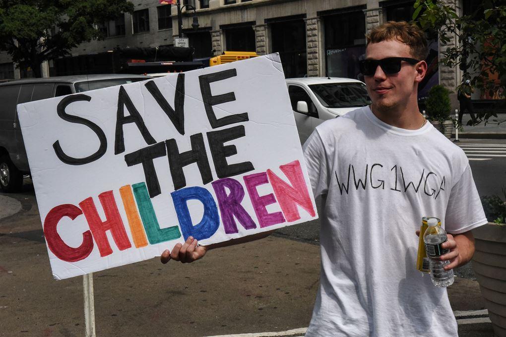 """Tilhænger af konspirationsteorien QAnon med et skilt med påskriften """"Save the Children"""""""