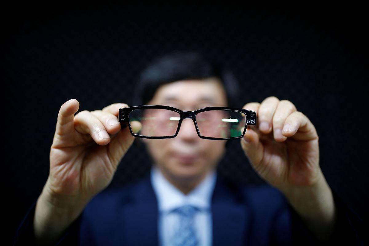 En mand i sløret baggrund holder et par briller frem