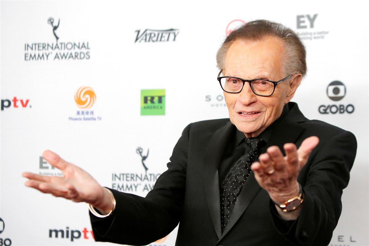 En ældre og svageligt udseende Larry King slår ud med sine arme