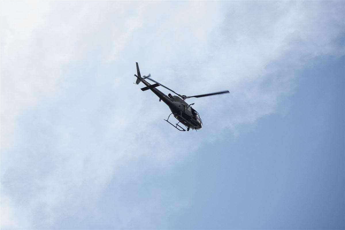 En politihelikopter i luften med blå himmel
