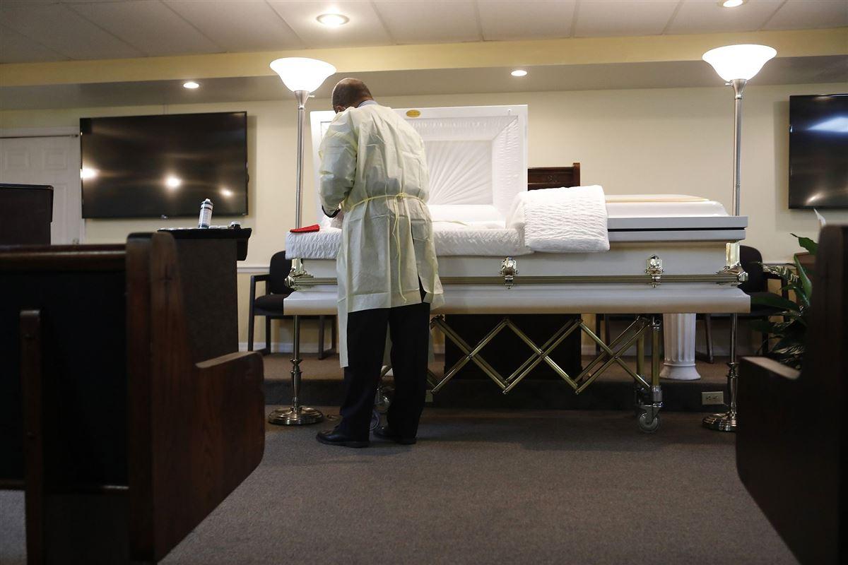 En bedemand står over en ikke synlig person, som loigger på en briks.