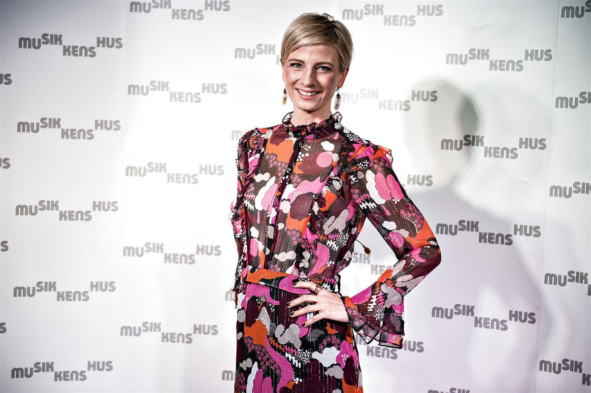 Tv-vært Louise Wolff smiler og kigger direkte ind i kameraet. Hun har en storblomstret kjole på og den ene hånd på hoften.