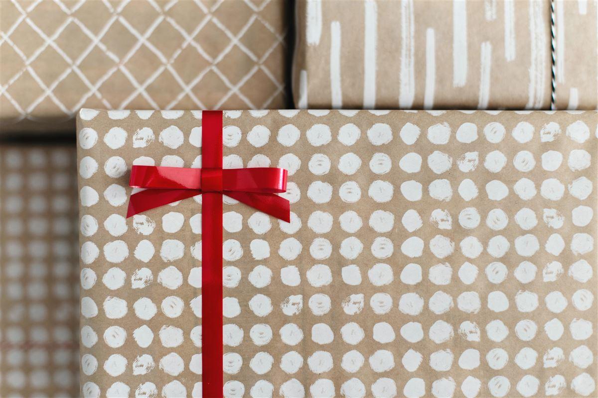 Pakker i pænt brunt og hvidt papir med rødt bånd om
