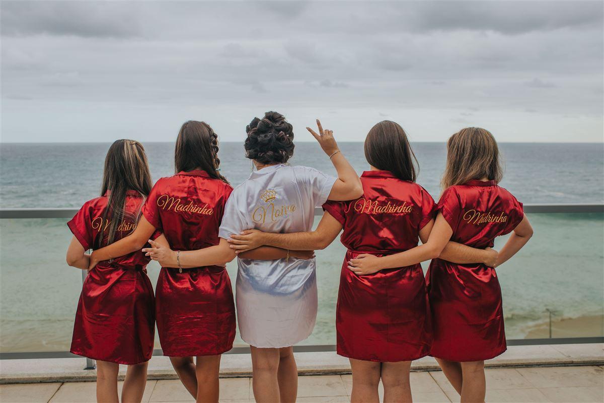 5 kvinder bagfra - fire af dem i røde silkekjoler - hende i midten har curlers og klædt i hvidt