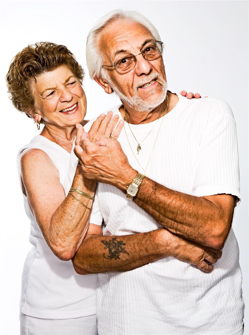 Et ældre ægtepar klædt i hvidt holder om hinanden