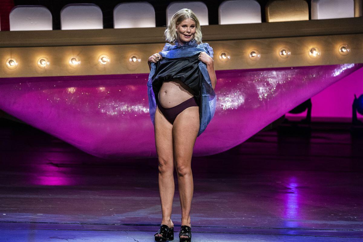 Gravid Sofie Linde løfter op i kjole og viser bar, gravd mave på scenen