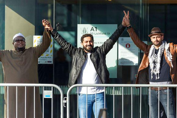 Tre mænd står med armene i vejret uden for retsbygning i New Zealand