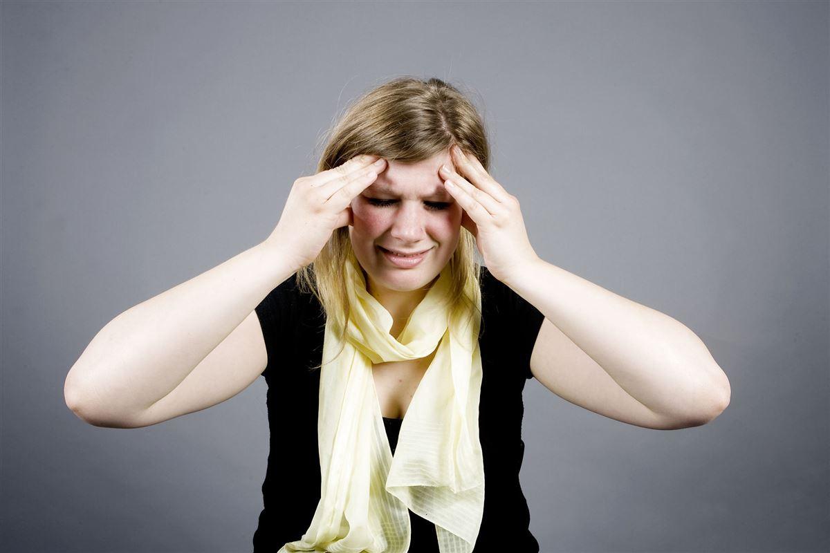 Kvinde med migræne tager sig til hovedet