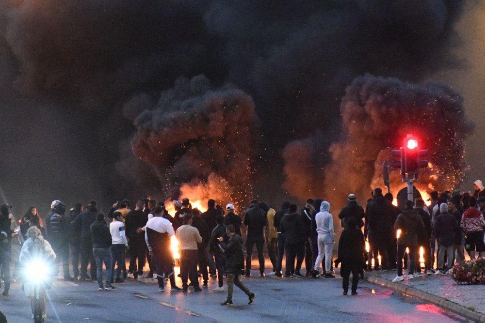 mennesker er samlet på gaden ved boligkvarteret Rosengården