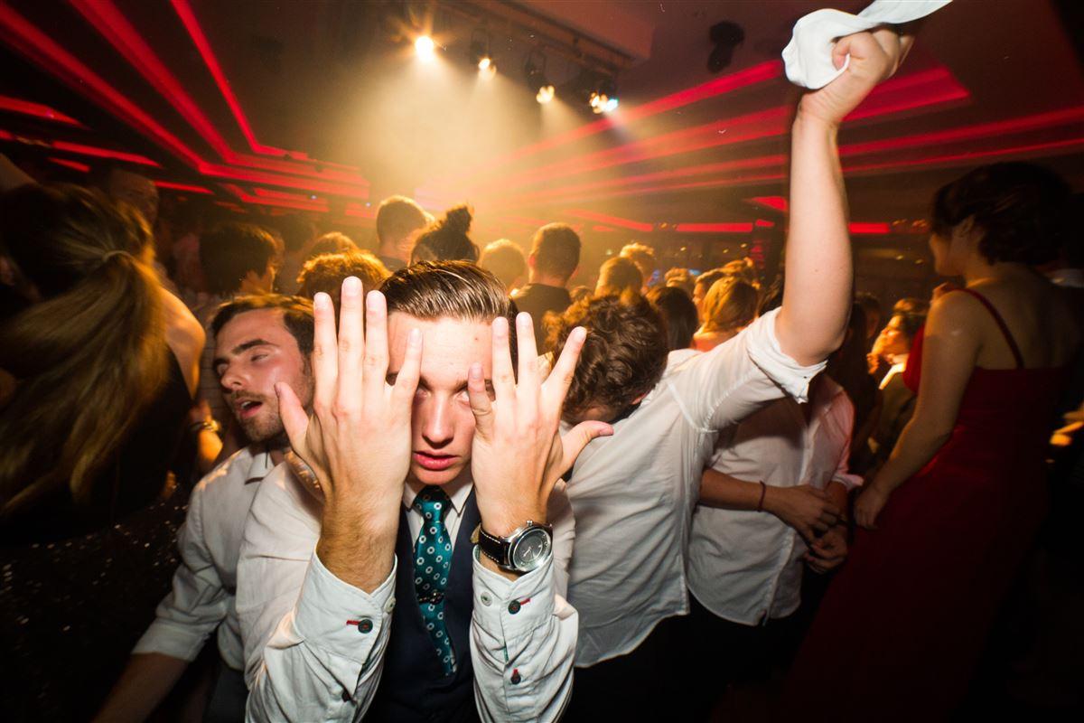 Fest med diskotekslys og ungen mænd og kvinder, som fester.