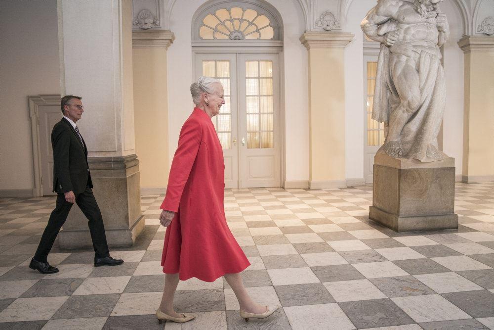 Dronning Margrethe i rød frakke går henover gulv