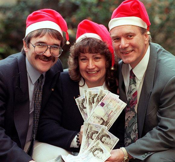 Tre personer med nissehuer griner bredt, mens de sidder med en sæk fyldt med pengesedler