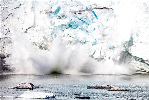 Store stykker is ryger ned i vandet fra en gletsjer