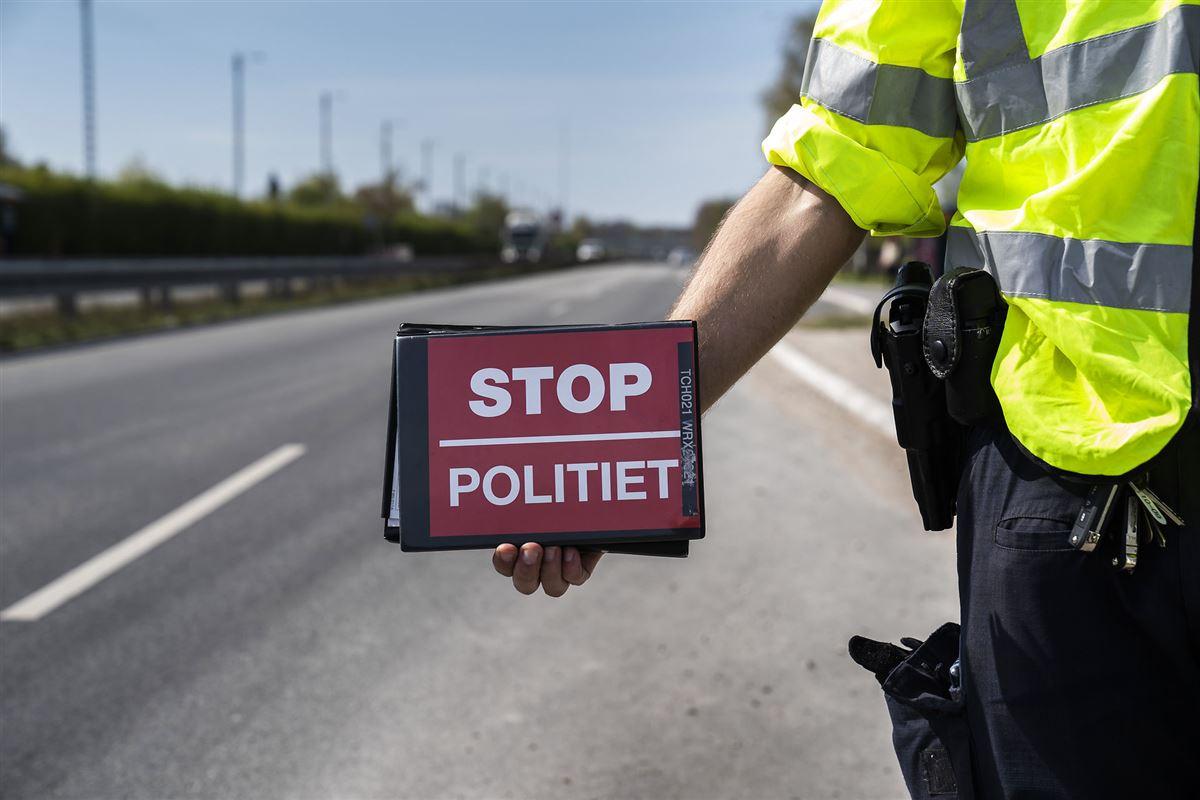 """Færdelsbejtent med skilt med påskriften """"Stop - Politiet"""""""