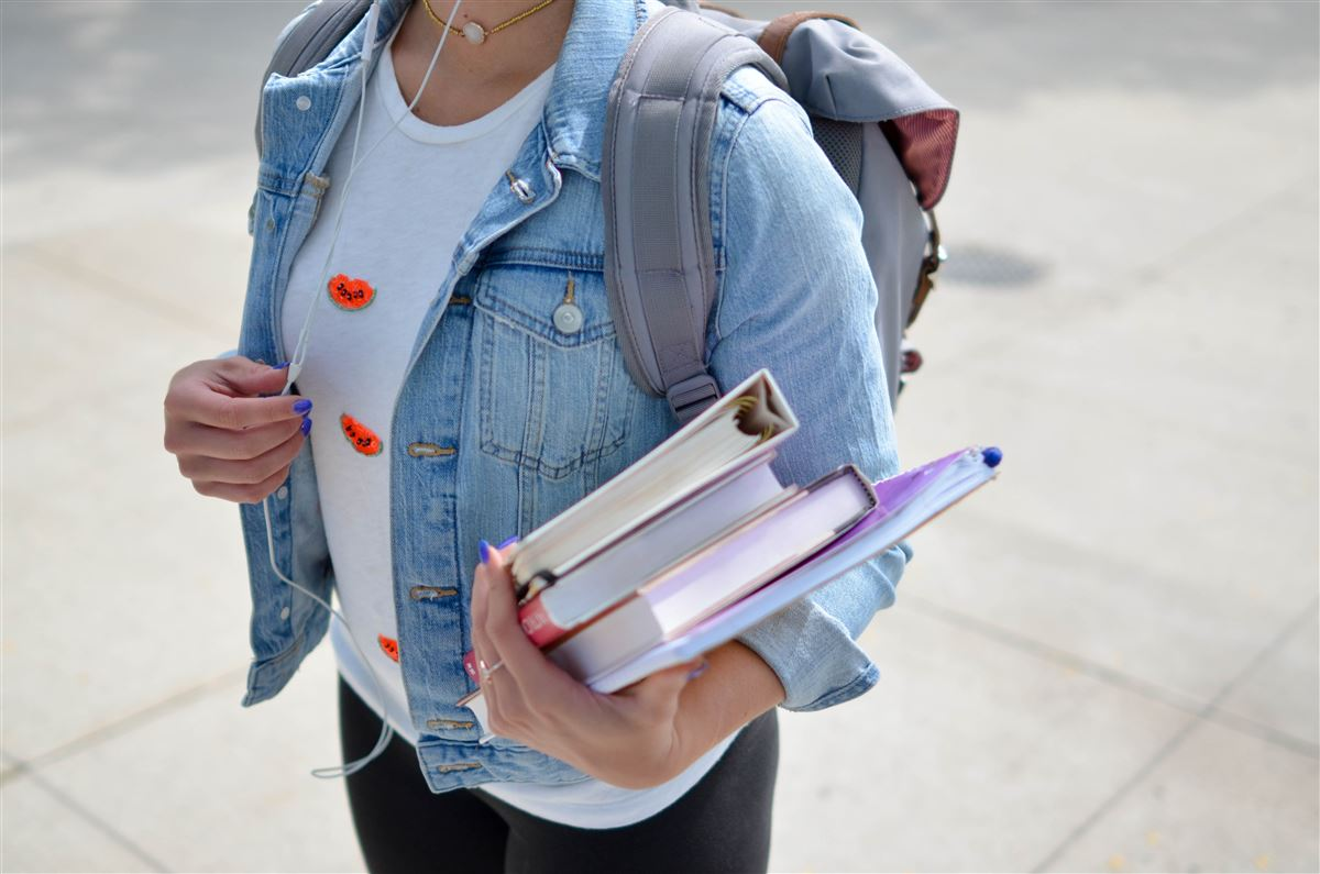 En kvindelig studerende i jeans-jakke med bøger i hånden