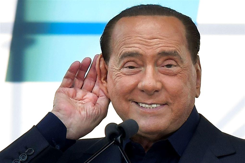 Silvio Berlusconi med hånd bag øret.