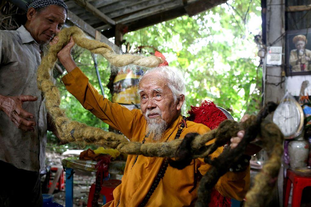 Den 92-årige Nguyen Van Chien sidder med en del af sit fem meter lange hår i hænderne.