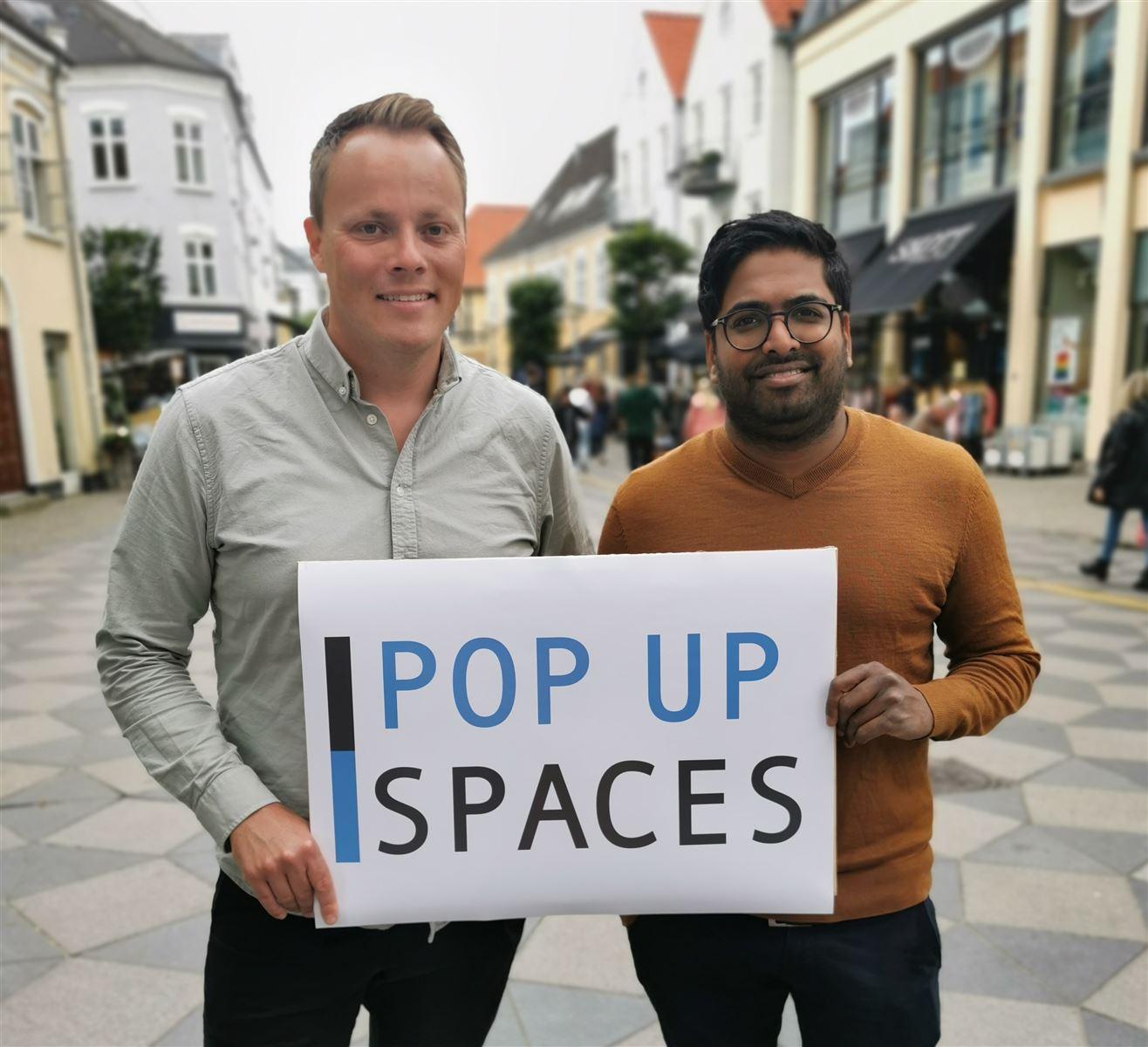 To mænd står på en gågade med et skilt, hvor der står Pop Up Spaces på