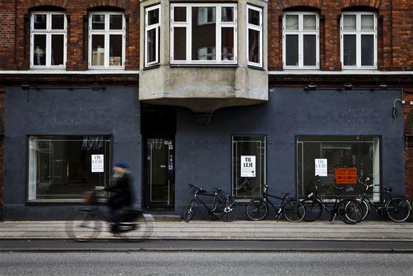 Tomme butikslokaler, hvor en cyklist cykler forbi