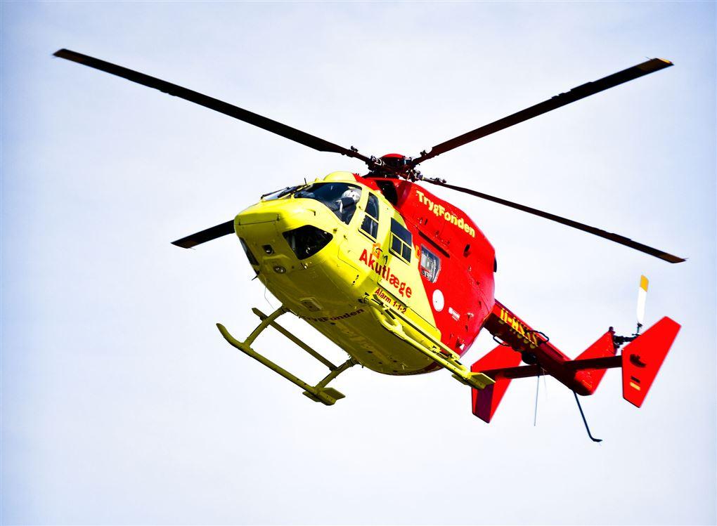 En rød og gul lægehelikopter i luften