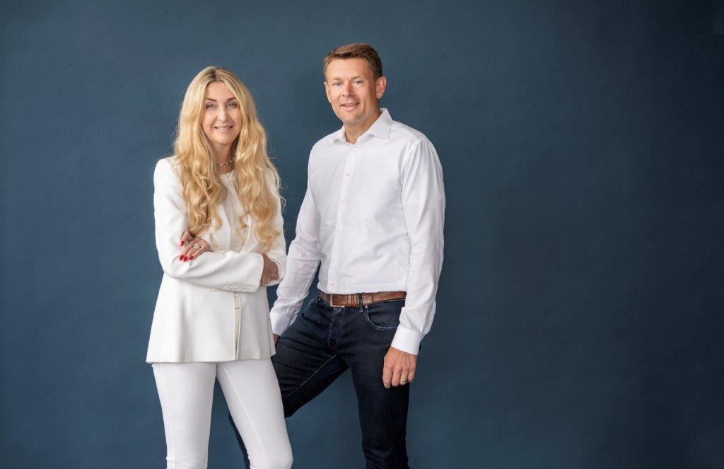 En blond kvinde klædt i hvidt ved siden af en mand med mørke bukser og hvid skjorte