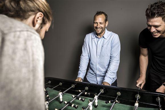 Martin Thorborg med to medarbejdere spiller bordfodbold