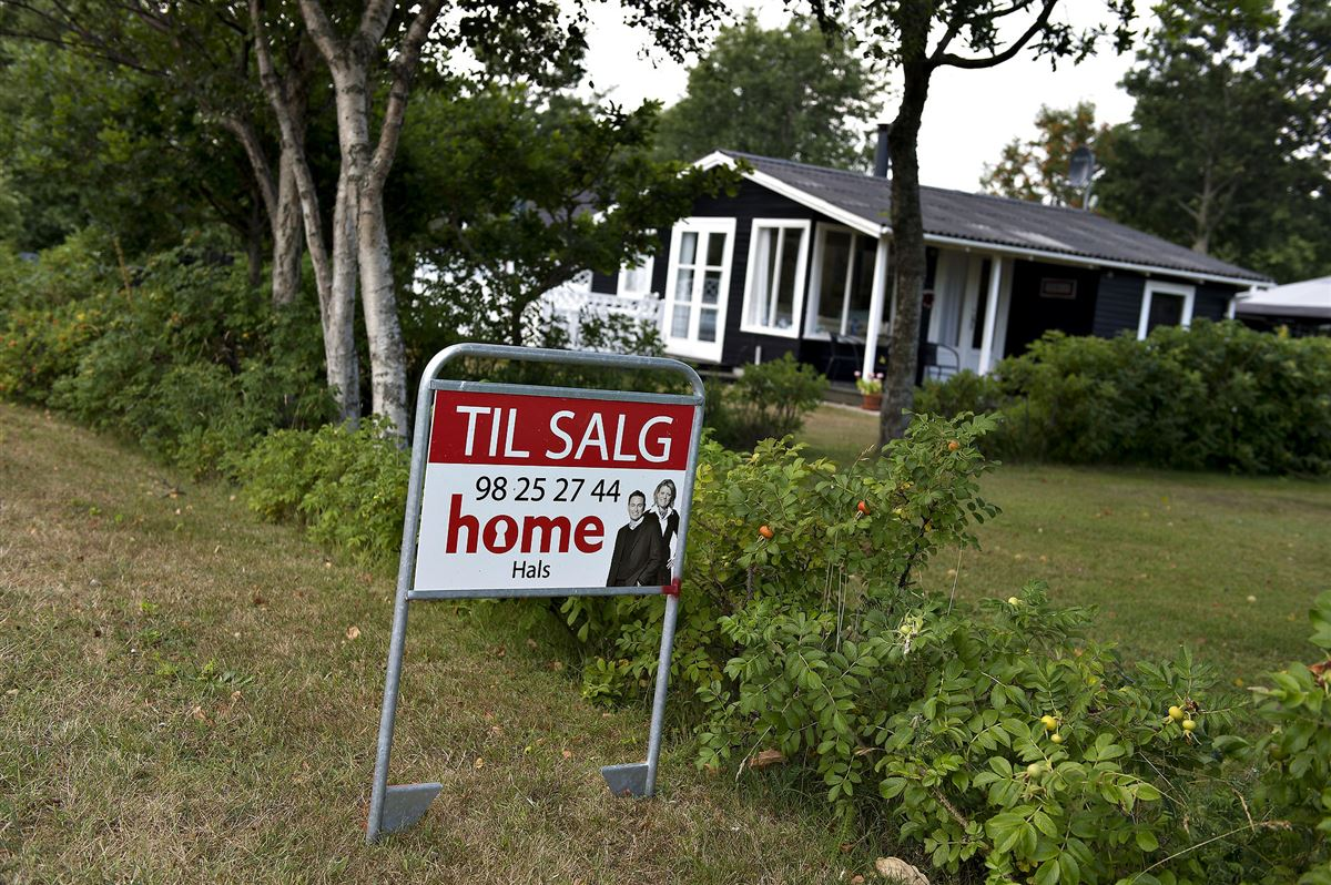 På billedet ses et sortmalet sommerhus med et til-salg-skilt foran fra Home
