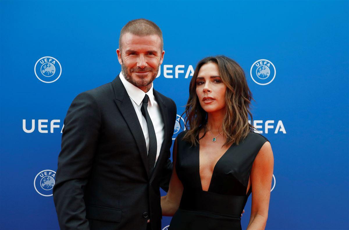 Fodboldstjernen David Beckham i jakkesæt sammen med sin kone Victoria Beckham, der har en stort kjole med dyb udskæring på.
