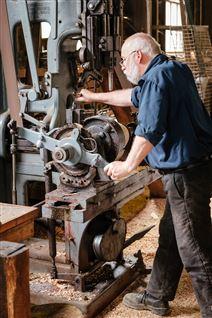 Ældre mand i arbejdstøj ved en stor maskine