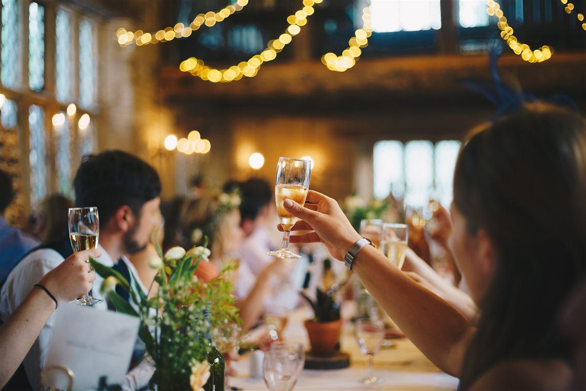 Mennesker med hævede glas ved bordet ved en festlig sammenkomst